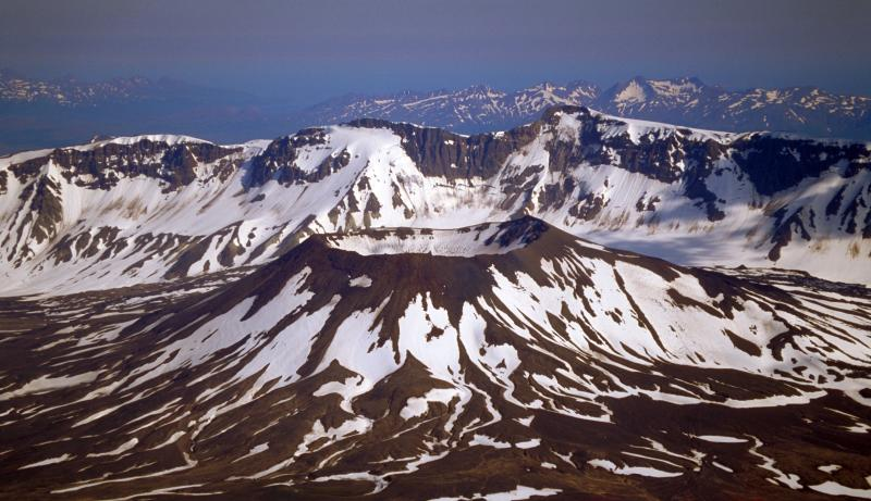 A snow covered small volcano and a mountain range behind it. Aniakchak National Monument