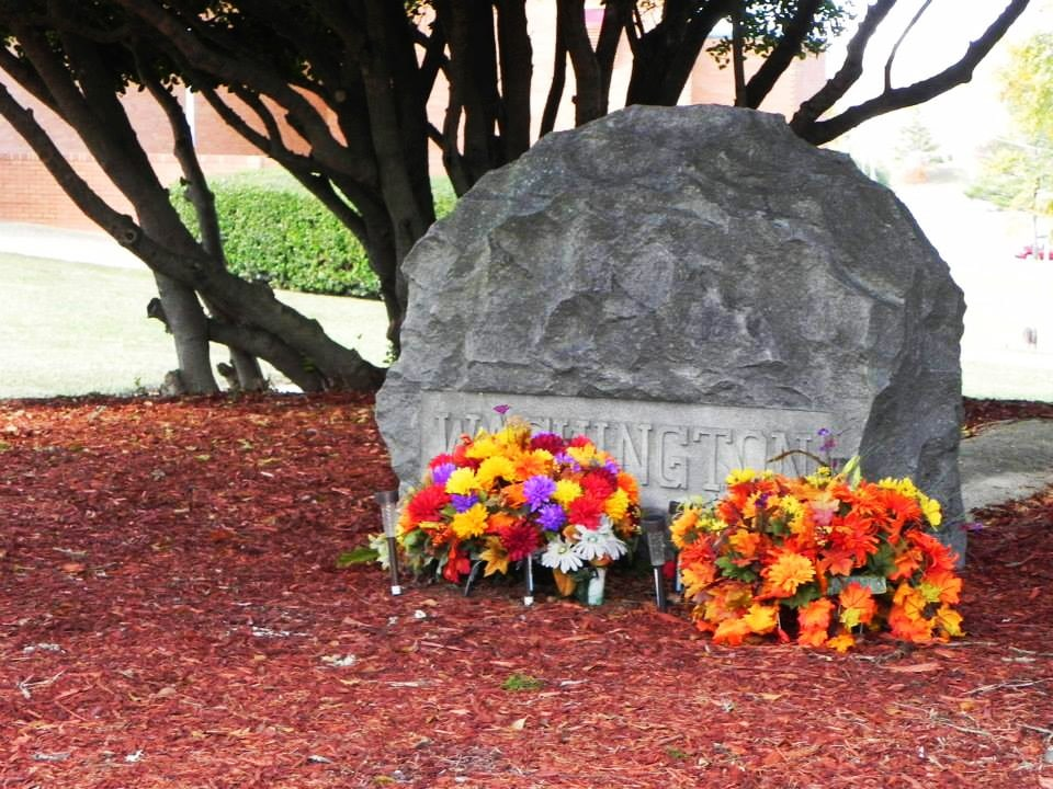 Booker T. Washington's grave stone with flowers at the base.