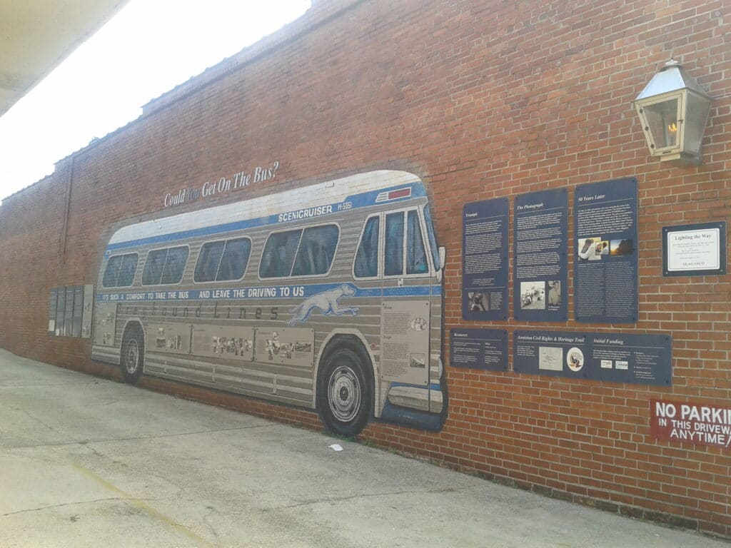 A mural of a greyhound bus on a brick wall