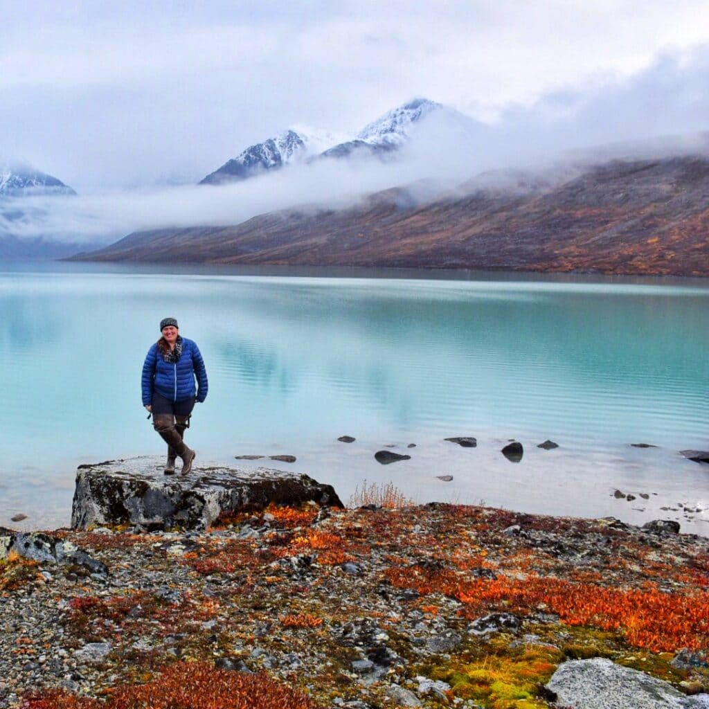 Jennifer (A woman) standing next to a turquoise blue lake in Alaska.