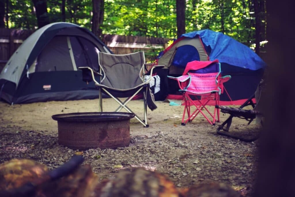 Two camp chairs by two tents.