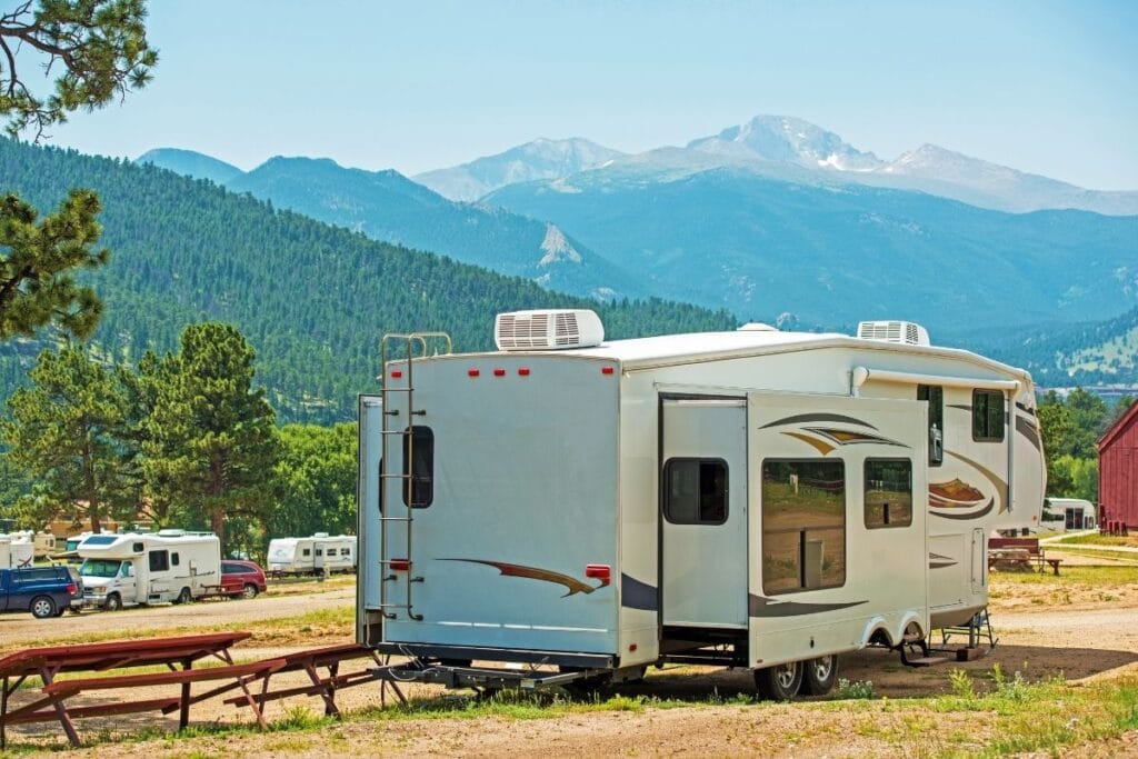 An Fifth Weel in a RV park with the mountains in the background.