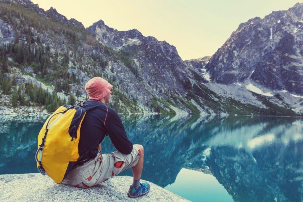 A man sitting by an alpine lake enjoying the mountain view.