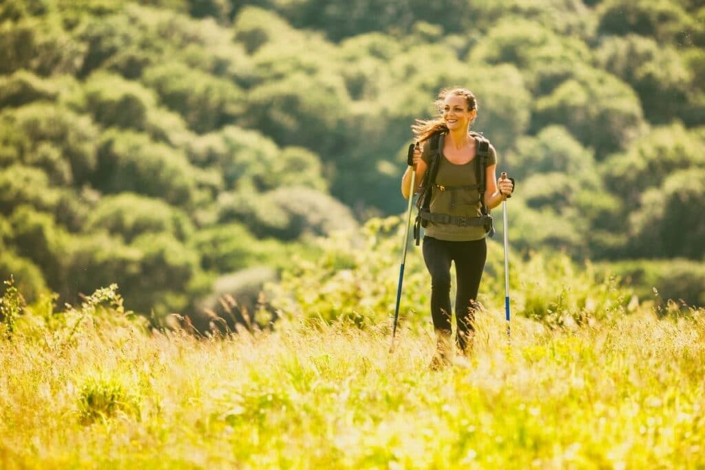 A woman hiking through a field of glass.