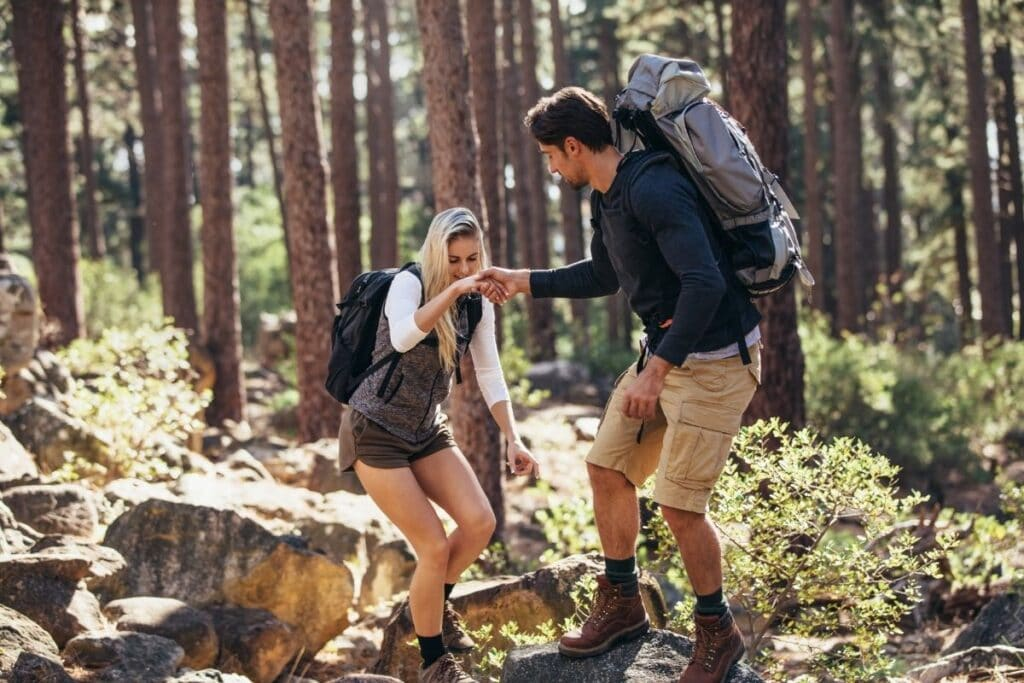 A man and woman hiking on some rocks.  The man is helping the woman up.