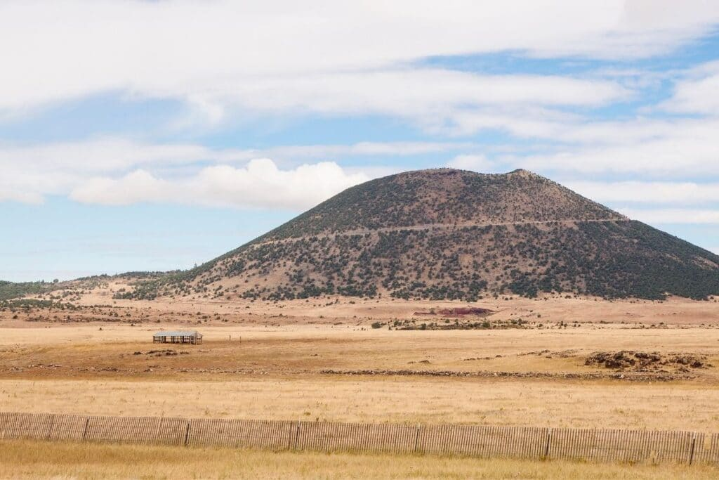 A cinder cone volcano next to a dry field